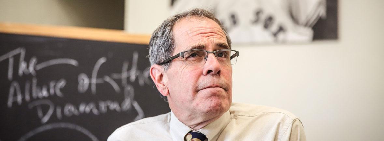 Professor Joe Price sits in front of a blackboard.