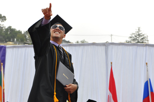 Graduate points to the crowd at Commencement.
