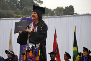 Female graduate crosses the stage at Commencement.