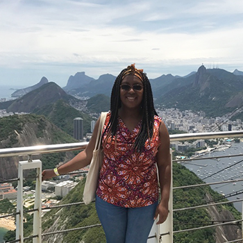 Anthropology major Esther Hills at a high point in Brazil, with mountains and a city behind her.