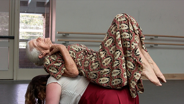 Two women performing a movement-based ritual of a fictive matriarchy