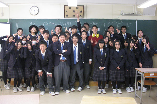 Robert Kondo poses for a photograph with a classroom of Japanese students.