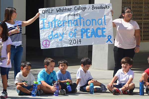 OMEP members hold up an International Day of Peace sign with students.