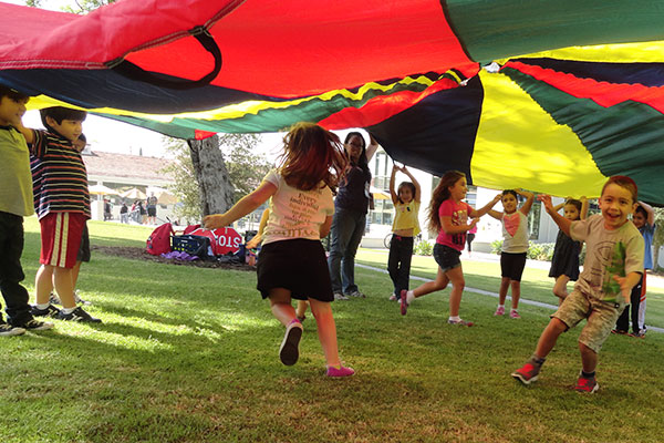 Students play under a tent top on the Whittier College campus.