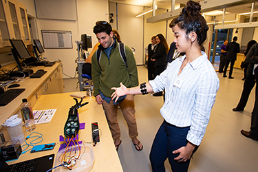 Kinesiology major Danica Cooley demonstrates a robotic arm.