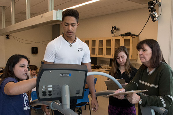 Students operating treadmill in movement lab