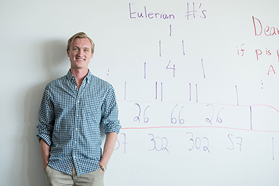Philip de Castro stands in front of a whiteboard with math equations written on it.