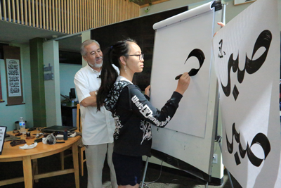 student creating calligraphy art on easel