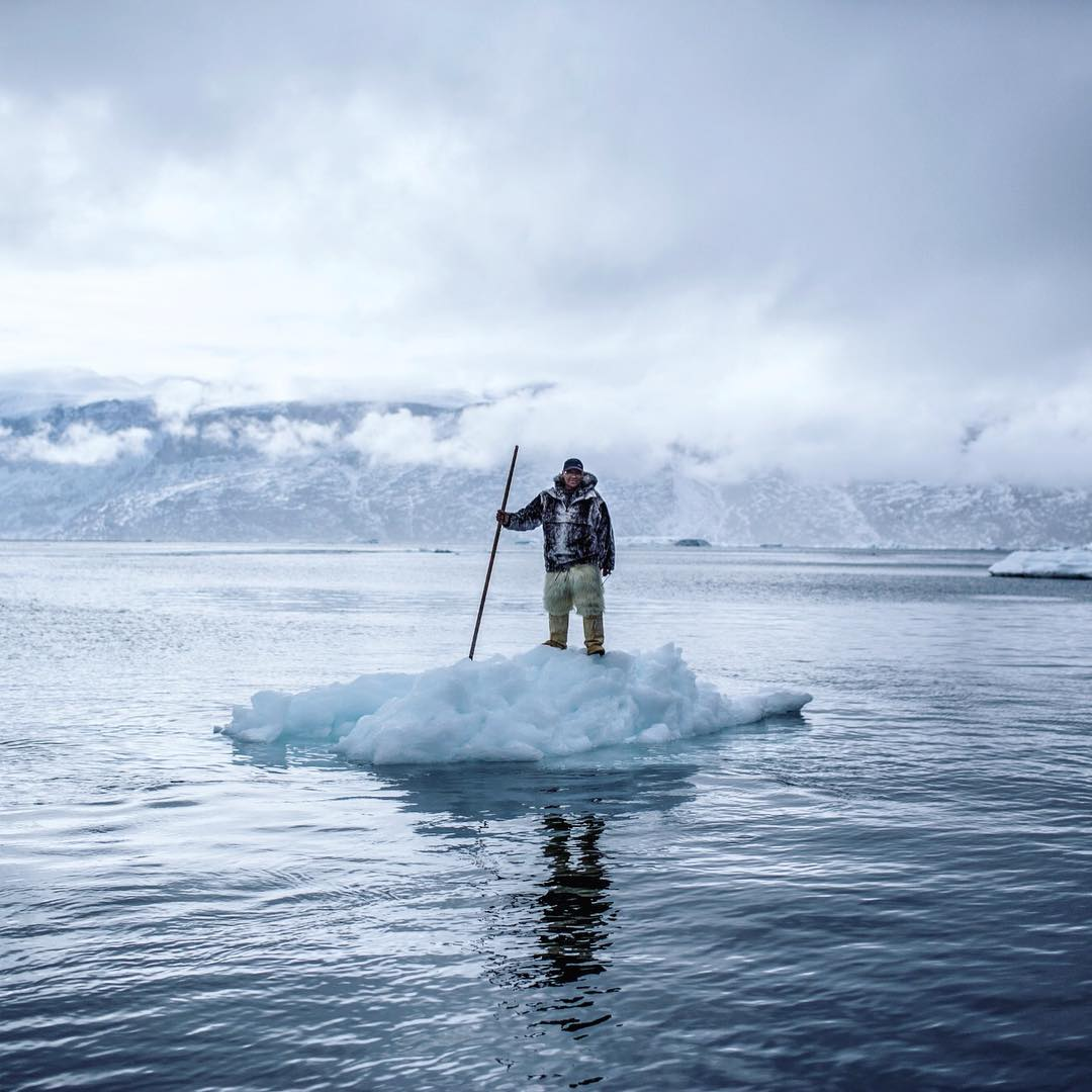 A man wearing a thick coat and pants stand on a floating ice berg in a lake surrounded by large icebergs