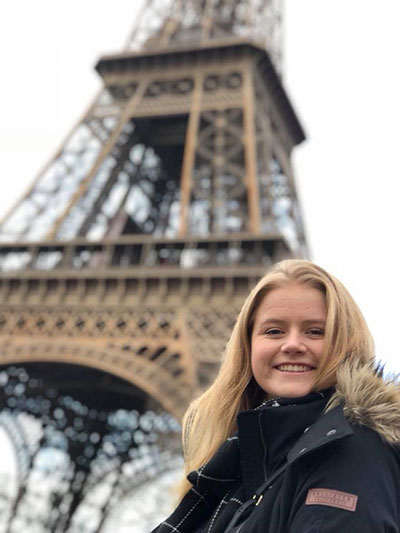Alyssa Hayne poses for a photograph in front of the Eiffel Tower.