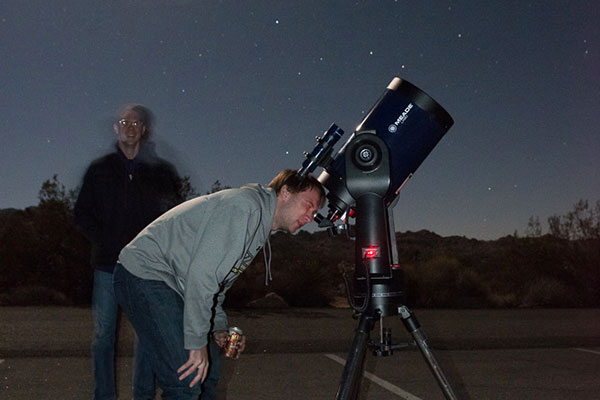 A student looks through a telescope at a star party.