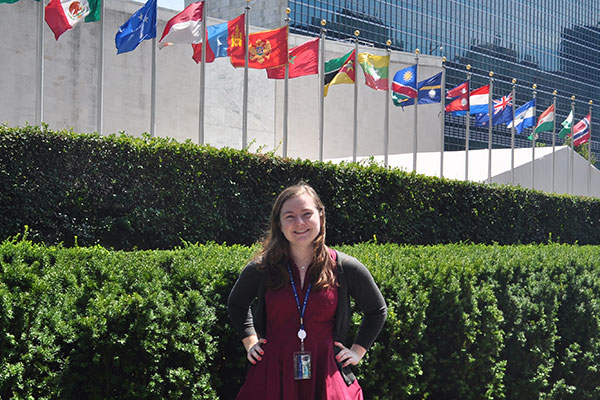 Political science student stands in front of United Nations flags.