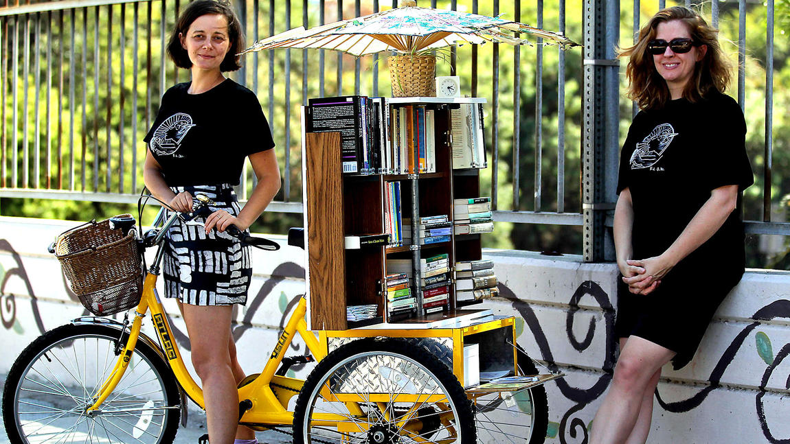 "Alumna Dawn Finley (right), Jenn Witte (left) and custom ""bookcycle"""