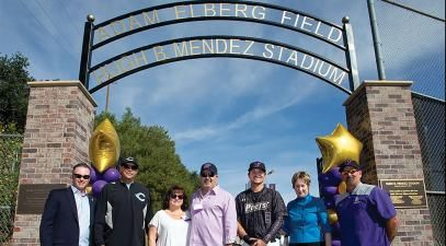 A group photo in front of the new Adam Elberg Field and Hugh B. Mendez Baseball Stadium.