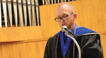Professor Sal Johnston, wearing academic regalia, gives a speech at a podium in Memorial Chapel.