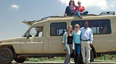 A group photo of five people in front of a jeep in Tanzania.