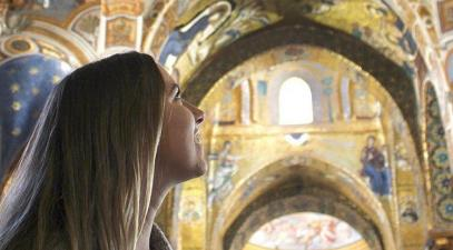 Student looks up at painted cathedral ceiling in Europe.