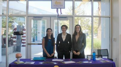 "Three women stand behind a table with a sign that reads ""Whittier College Established 1887"""