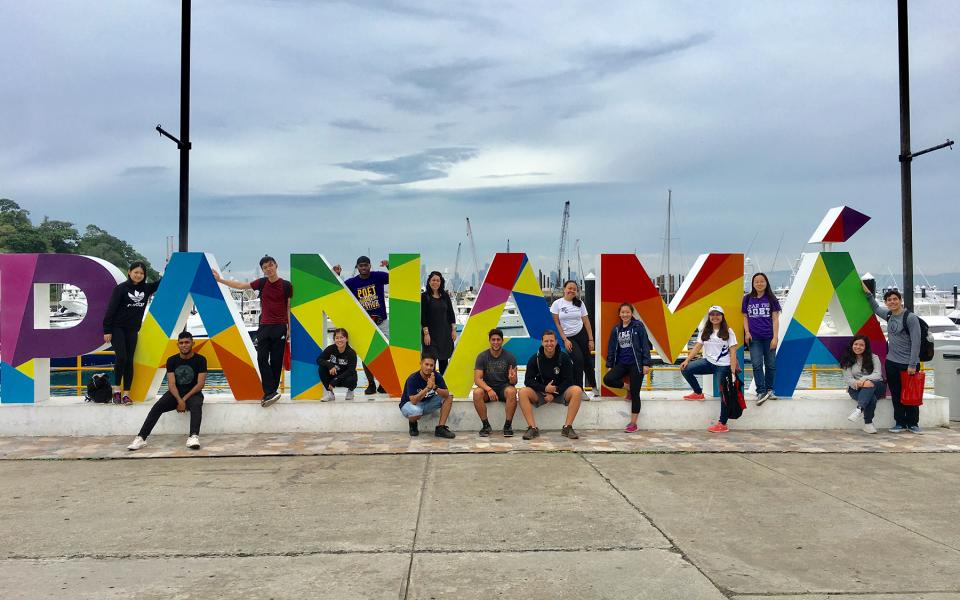 Students and professor Sylvia Vetrone pose for a photo among giant letters spelling Panama.